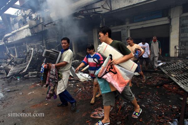 Sejumlah pedagang berusaha mengamankan barang dagangannya dari kobaran api yang membakar kios mereka di Pasar Klewer, Solo, Jawa Tengah, Minggu(28/12).
