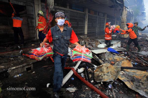 Sejumlah pedagang dibantu petugas berusaha mengamankan barang dagangannya dari kobaran api yang membakar kios mereka di Pasar Klewer, Solo, Jawa Tengah, Minggu (28/12).